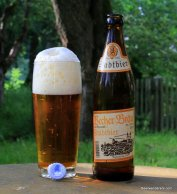 amber beer in glass with huge head and bottle