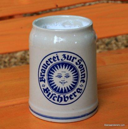 beer in ceramic mug with sun logo