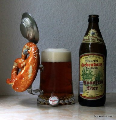 dark beer in mug with pewter lid and pretzel with bottle
