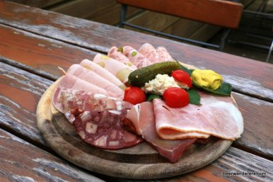 cold cuts on wooden plate with pickel