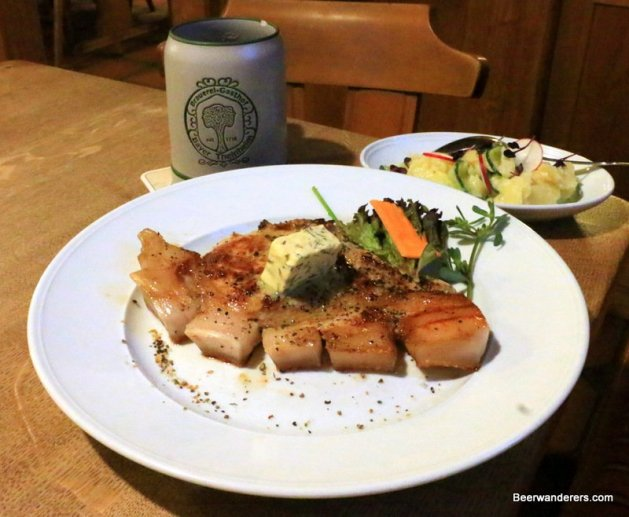 pork cutlet with herb butter on top with a beer in ceramic mug