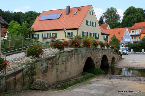 old stone bridge adorned with flowers