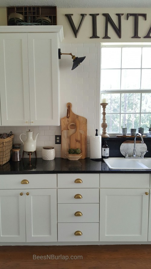 white cabinets sconce light industrial gold hardware kitchen