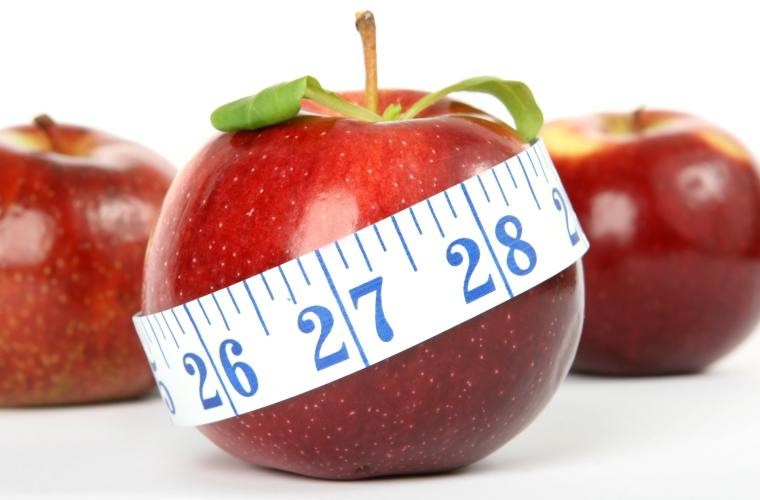 Measuring tape wrapped round an apple.