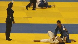 Referee signaling victory for the Judoka in the blue gi