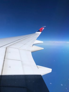 view over an airplane wing with the Delta logo on the wingtip, over the Pacific Ocean