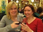 Deirdré and Robyn toasting at a restaurant in Paris