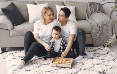 Family eating pizza on a rug
