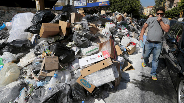 A man covers his nose as he walks past a pile of garbage along a street in Beirut, Lebanon July 22, 2015. The streets of Beirut are quickly becoming host to growing mountain of garbage after a crisis in the gvernment's waste management policy led to a halt in garbage collection and raising concerns for health and environmental adverse effects. REUTERS/Jamal Saidi