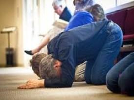 people on knees praying