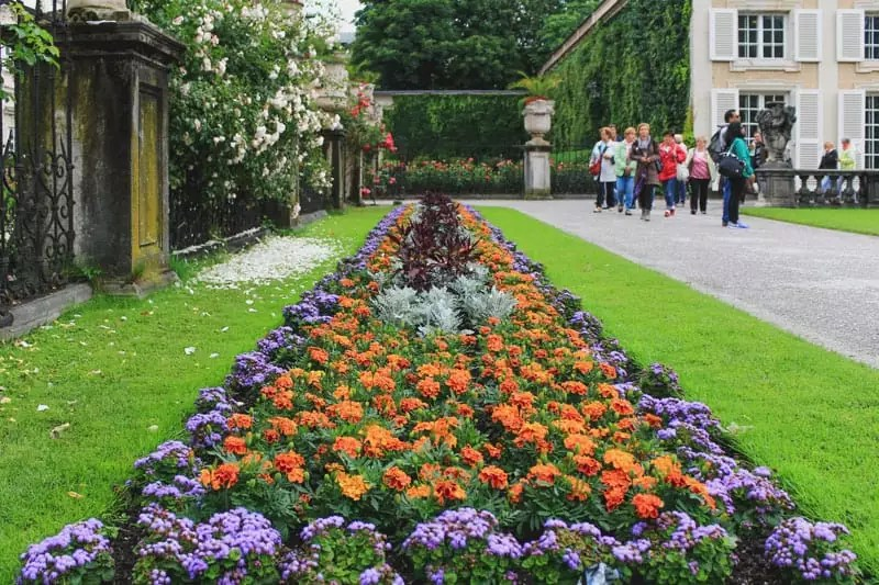 salzburg austria sound of music tour palace gardens tourists ornate formal landscaping flowerbed flowers