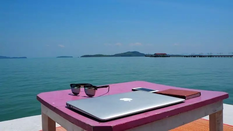 laptop on beach, Digital Nomad Tools
