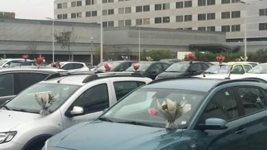 صورة بائعة زهور تضع مئات الباقات على سيارات مقدمي الرعاية