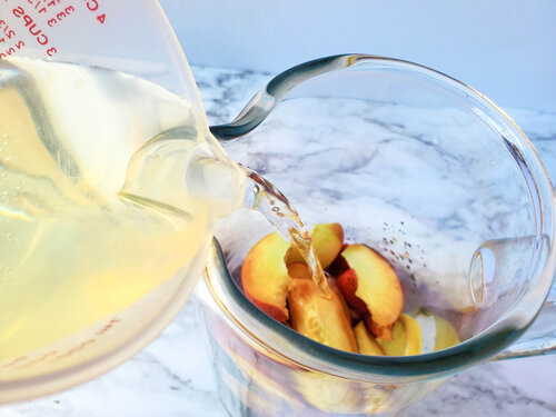 wine being poured into the pitcher of fruit sangria