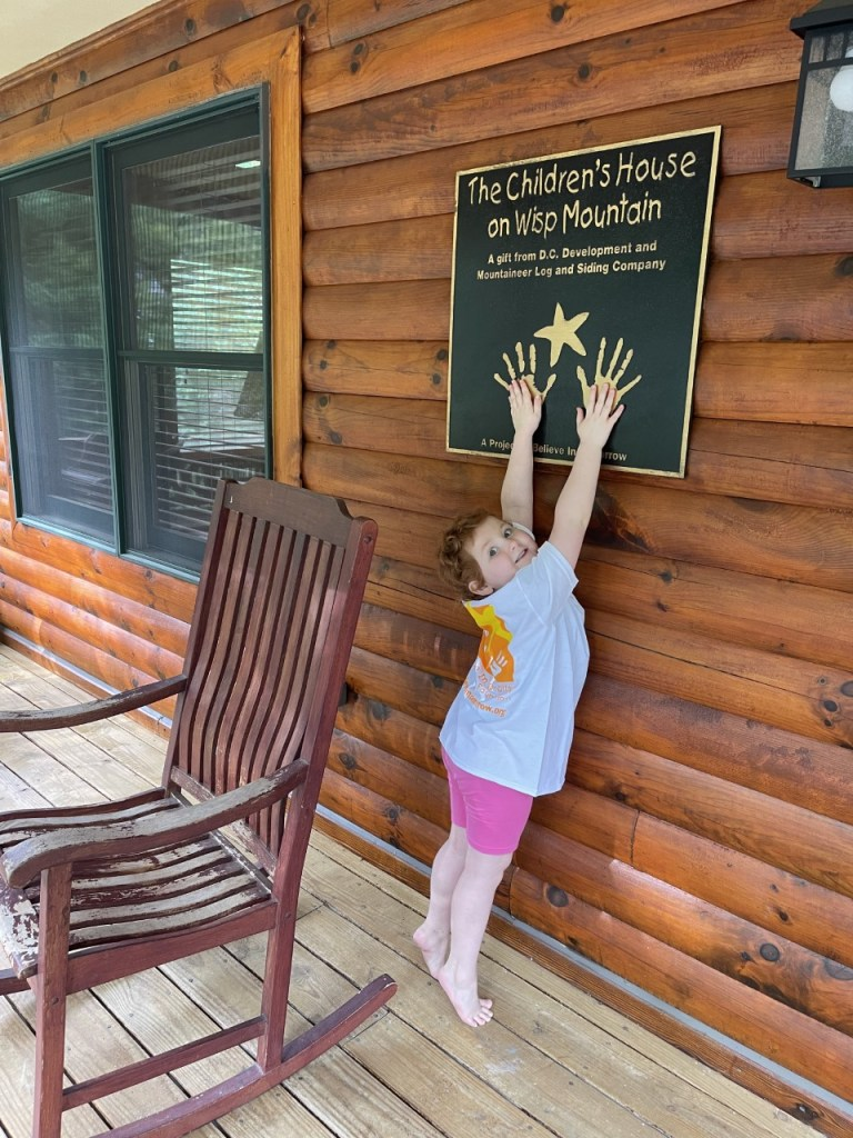 a young girl smiling on the porch of the children's house at wisp mountain