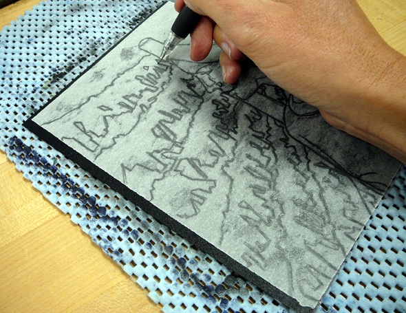 a hand drawing on a thin sheet of paper laid on top of an inked plate with a technical pencil