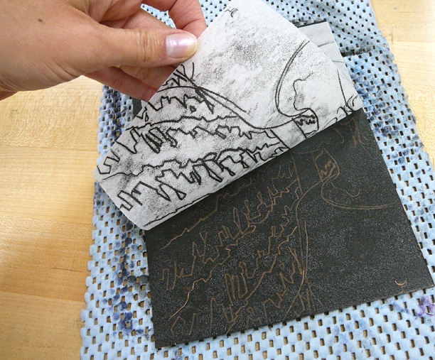 a hand pulling a sheet of paper off a rectangular plate coated with black ink