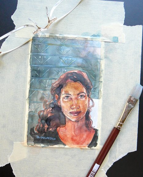A small watercolor portrait of a woman's face, looking directly at the viewer