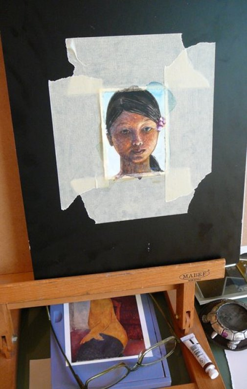 A tiny portrait of a face in watercolor, taped to a board in a studio, in process