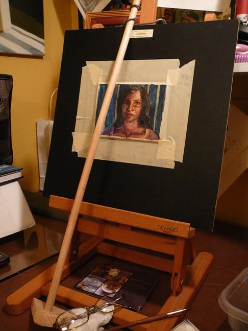 a desktop easel with a mahl stick and the beginnings of a small watercolor portrait