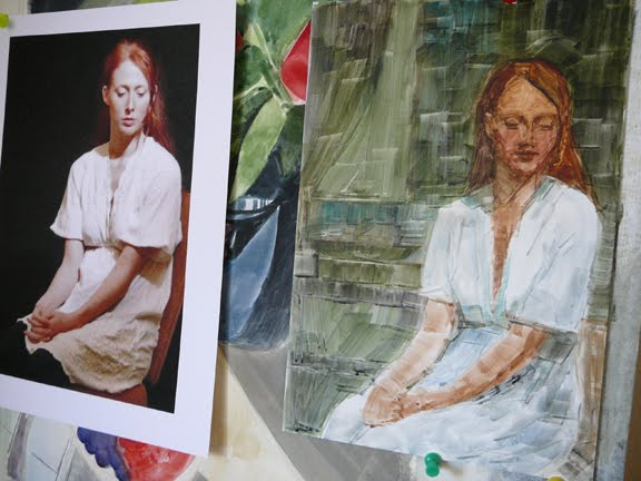 a watercolor portrait in process. next to the reference photo, in an art studio