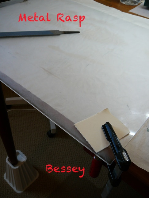 a sheet of polycarbonate clamped to a table being sanded on the surface, and beveled around the edges with a rasp.