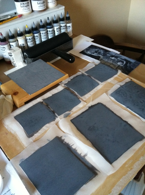 an artist's studio with silk screen adhered to small rectangular plates using black acrylic paint