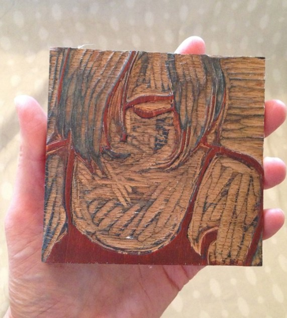 A wood block with a carving of a woman's face