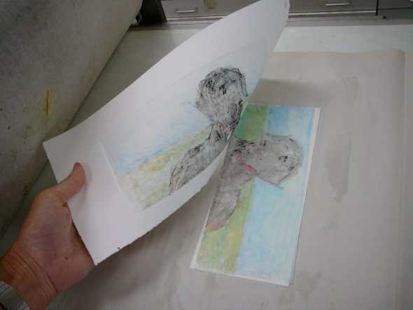 Pulling a sheet of paper off a a piece of drafting film that was colored with water-soluble crayon after a trip through the press. The pigments have been transferred to the paper as a result of the pressure.