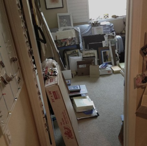 a room with a mess of boxes ans stacks of art supplies to be put away
