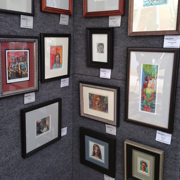 watercolors and printmaking art displayed on panels at an art festival