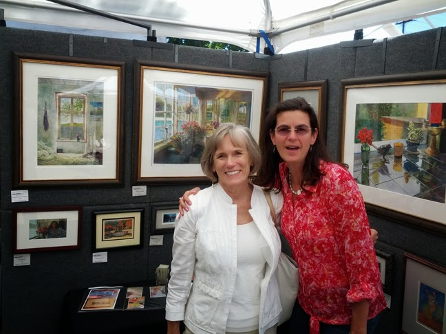 The artist with her arm around a woman standing inside a booth surrounded by paintings at an art festival
