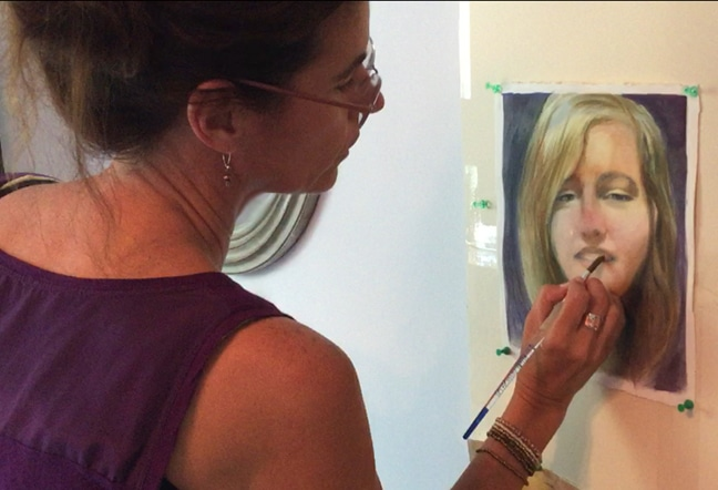 an artist painting a portrait in watercolor standing upright while the work in process is tacked to a wall