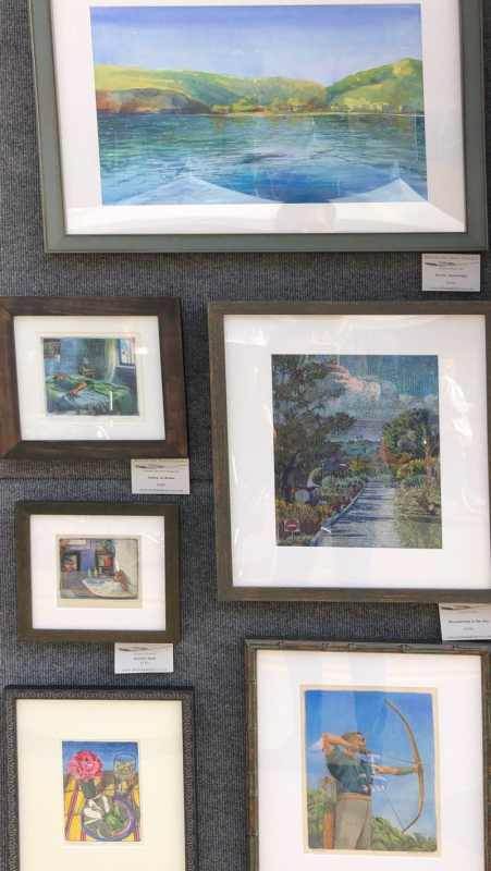 an artists paintings and hand pulled prints, framed na on display in a booth at an art festival