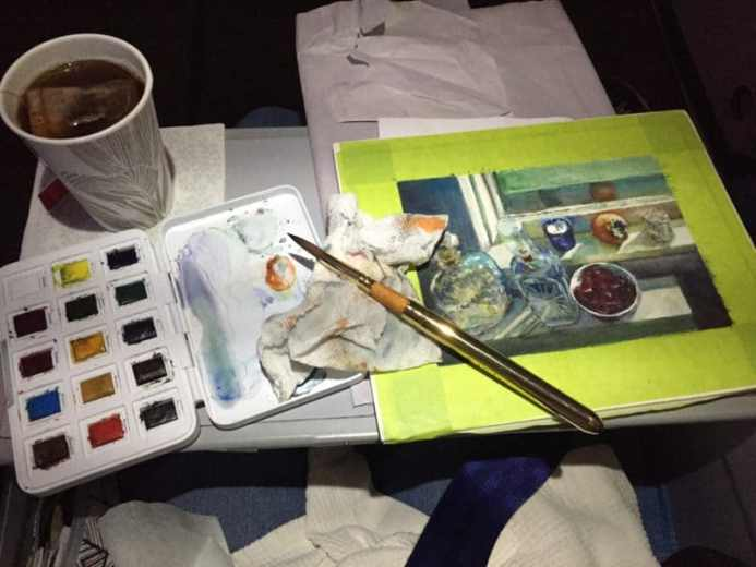 an airplane tray table with a cup of tea, a small travel palette of watercolors and a still life painting in process