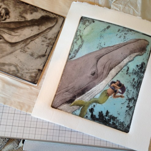 printmaking on a press bed - the intaglio drypoint plate next to the resulting print of a whale and a mermaid
