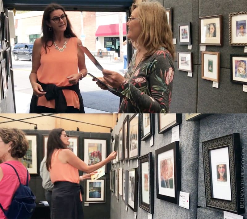 an artist inside an exhibit booth showing patrons the plates used to make collagraph prints framed on the walls