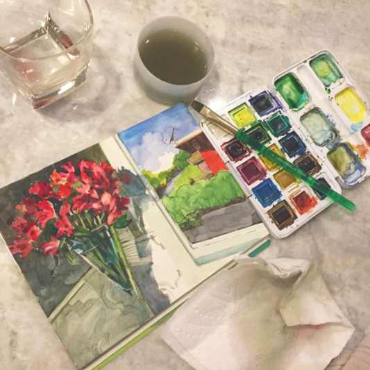 A watercolor sketch on a kitchen counter next to a small travel palette, a rinse cup for the paint, a brush and an empty glass of wine