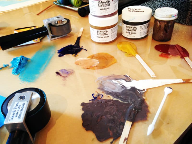 blobs of ink on a plexiglass covered work surface, with printmaking and inking tools around