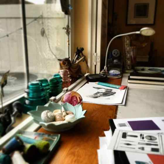 an artist's studio table at a window with printmaking, drawing and painting supplies