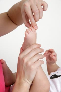 Behandlung der Baby-Füße mit Shiatsu