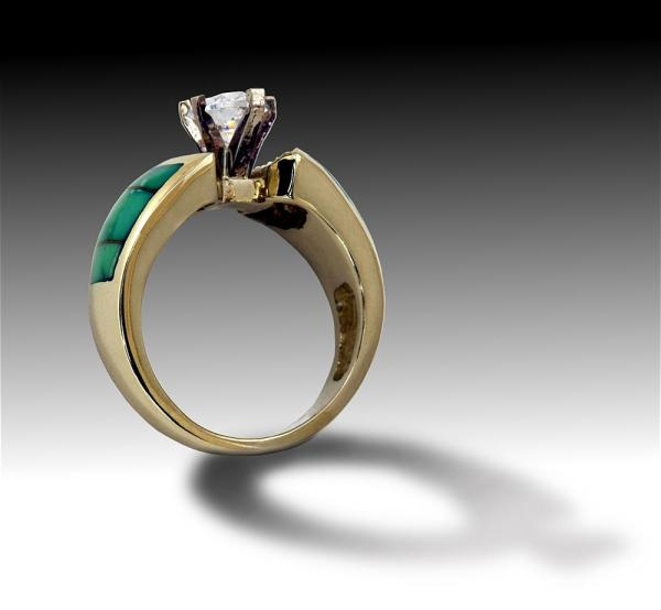 Three quarter view of gold ring with diamonds and turquois inlay