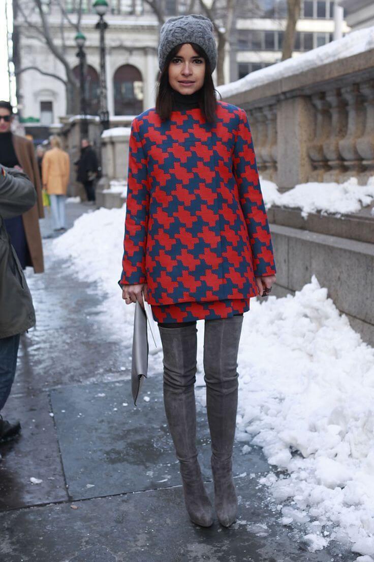 Miroslava Duma in a mod style printed dress, thigh high boots, and a knit beanie