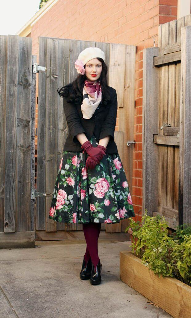 Woman wearing a floral skirt, black jacket, maroon leggings, gloves and a beret