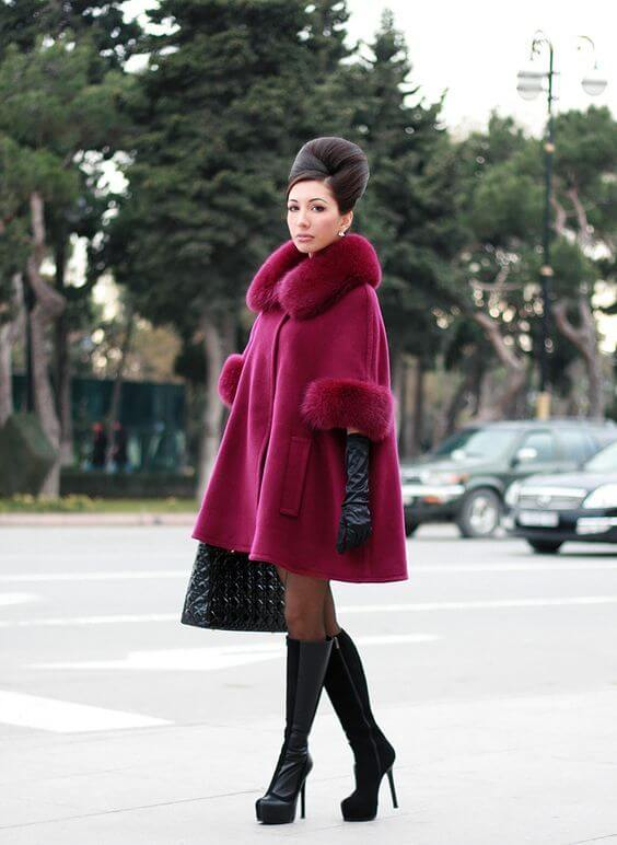 Woman wearing an oxblood swing coat, black knee length boots, and black gloves