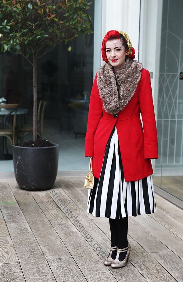Woman wearing a striped skirt, red coat, fur collar, and a fascinator