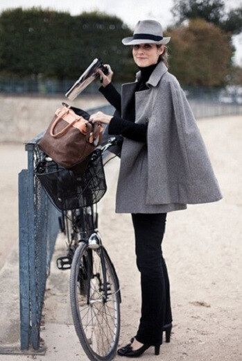 Woman with a bicycle wearing black pants, a grey cape coat, and a grey fedora
