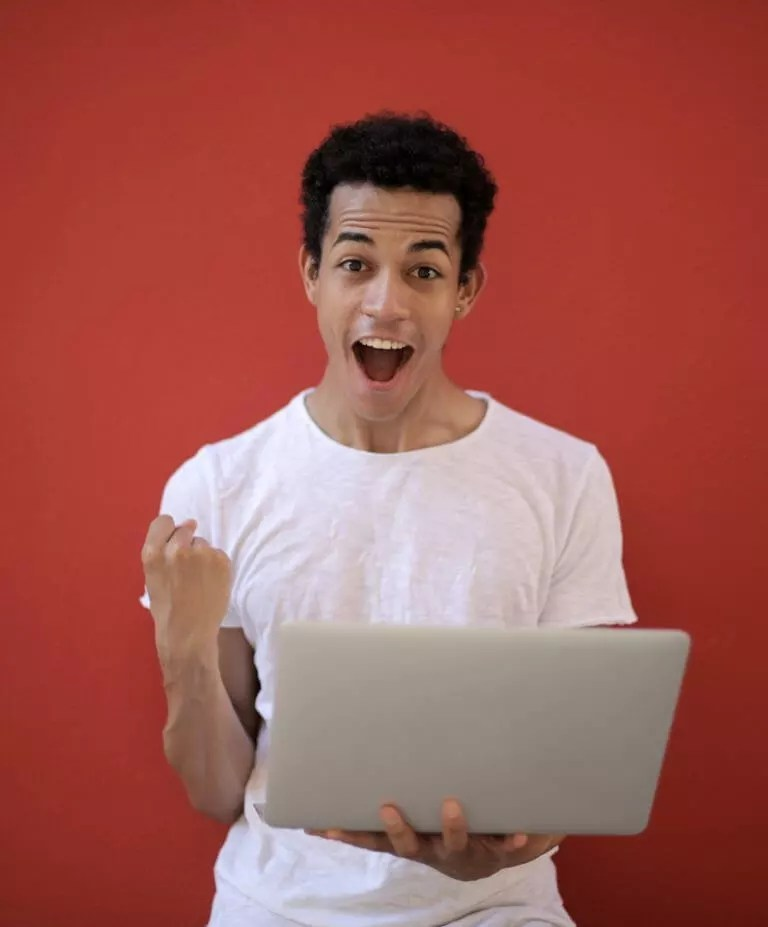 man looking at a laptop and excited