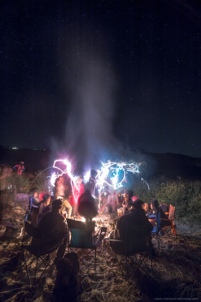 A group of beachgoers plays with sparklers in front of a fire, Cape Kiwanda, Oregon coast.