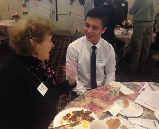 Veteran church member Caroline Farley talks to Senior Rodrigo Saldana.